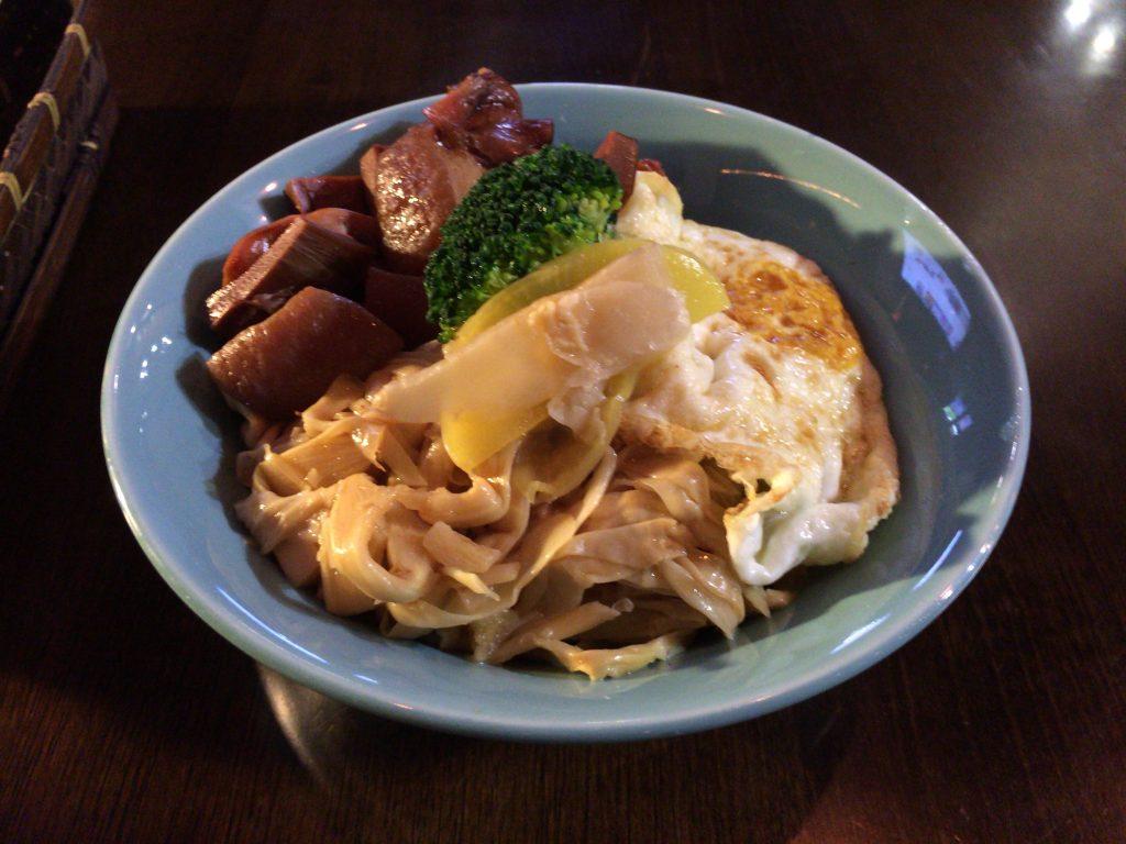 琉球丼。豚肉、イカ、卵、タケノコ、ブロッコリー、漬け物が乗っている