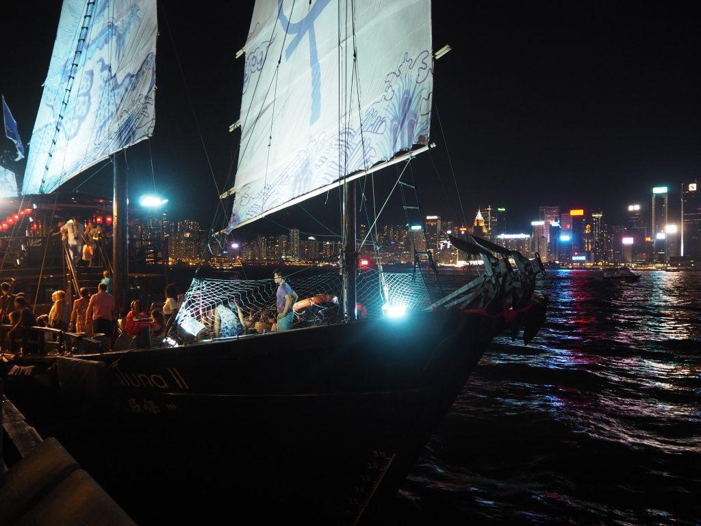 ビクトリアハーバーの夜景をバックに船が出航する