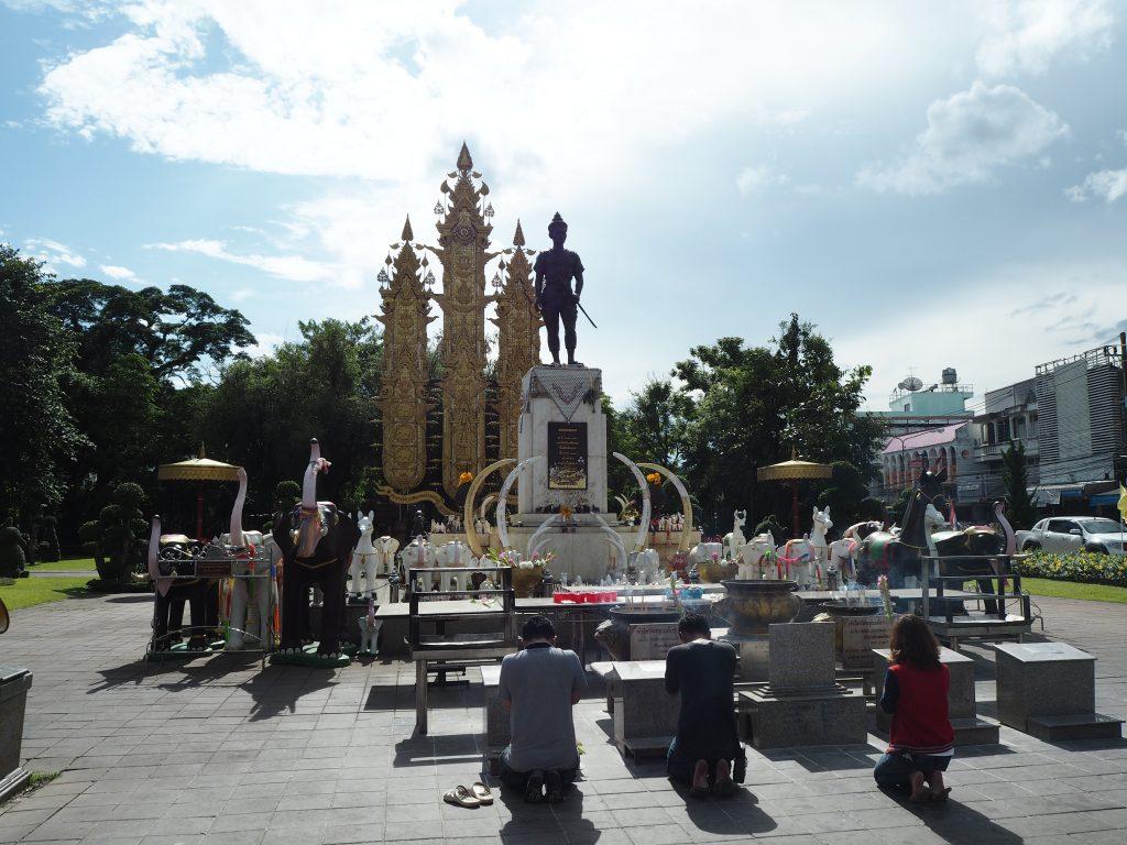 王像の前には献花をして祈りを捧げる人々がいる
