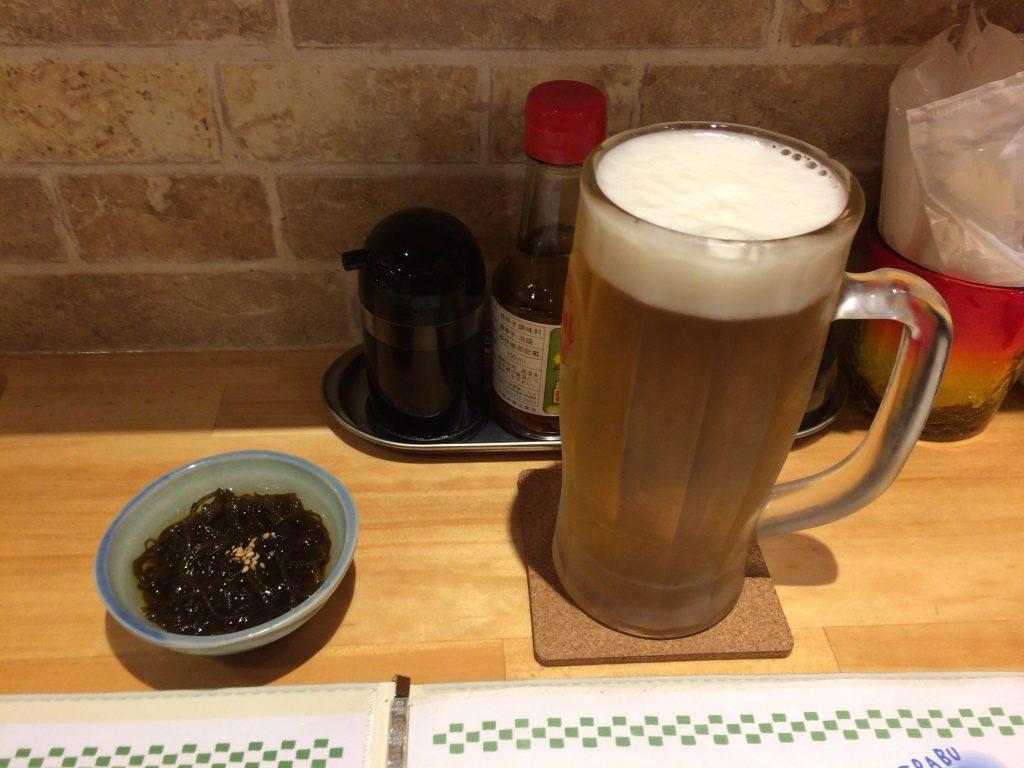 生ビールとお通し。与論島ではお決まりのもずくだ