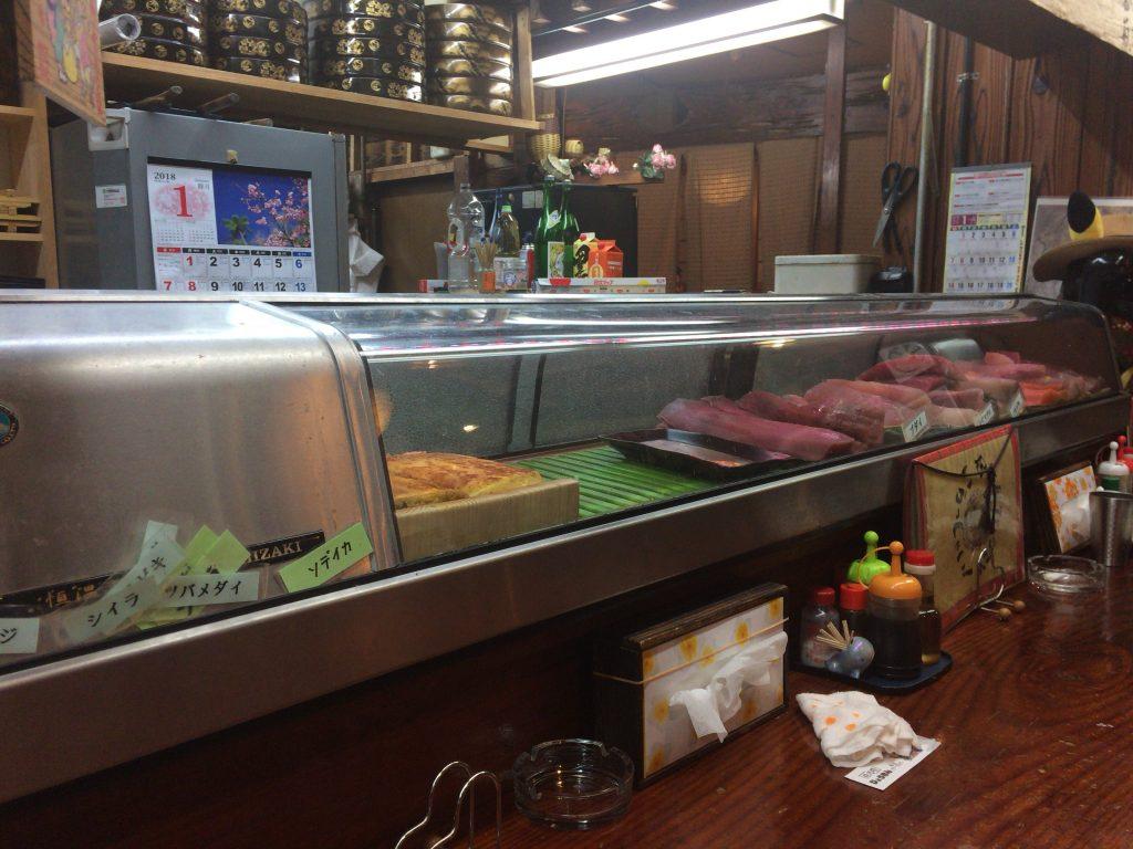 「居酒屋ひょうきん」のカウンター席。ケースには新鮮な魚が並ぶ