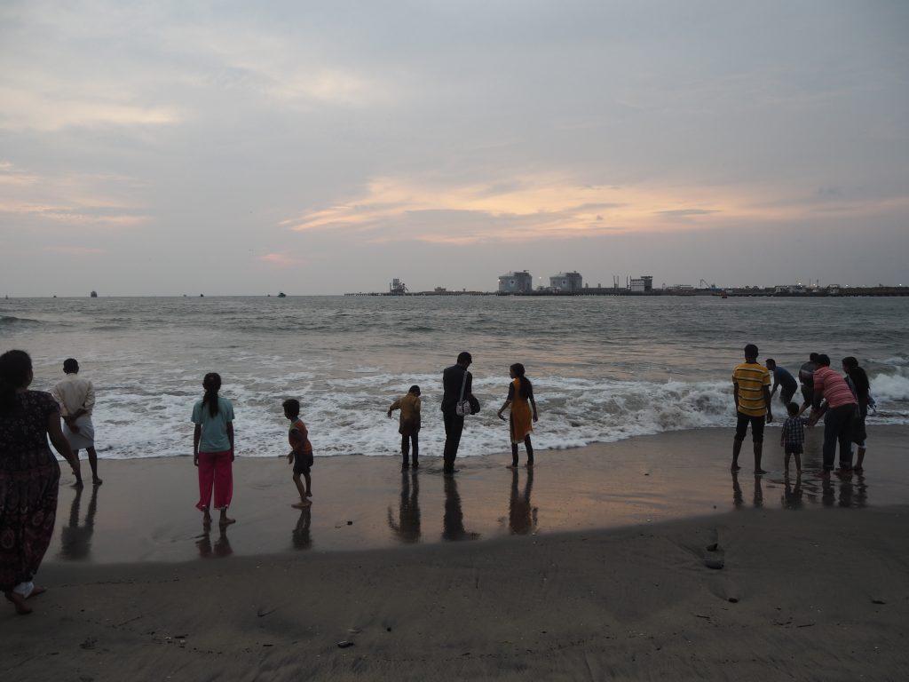 波打ち際で水遊びをしながら夕日を眺める人たち