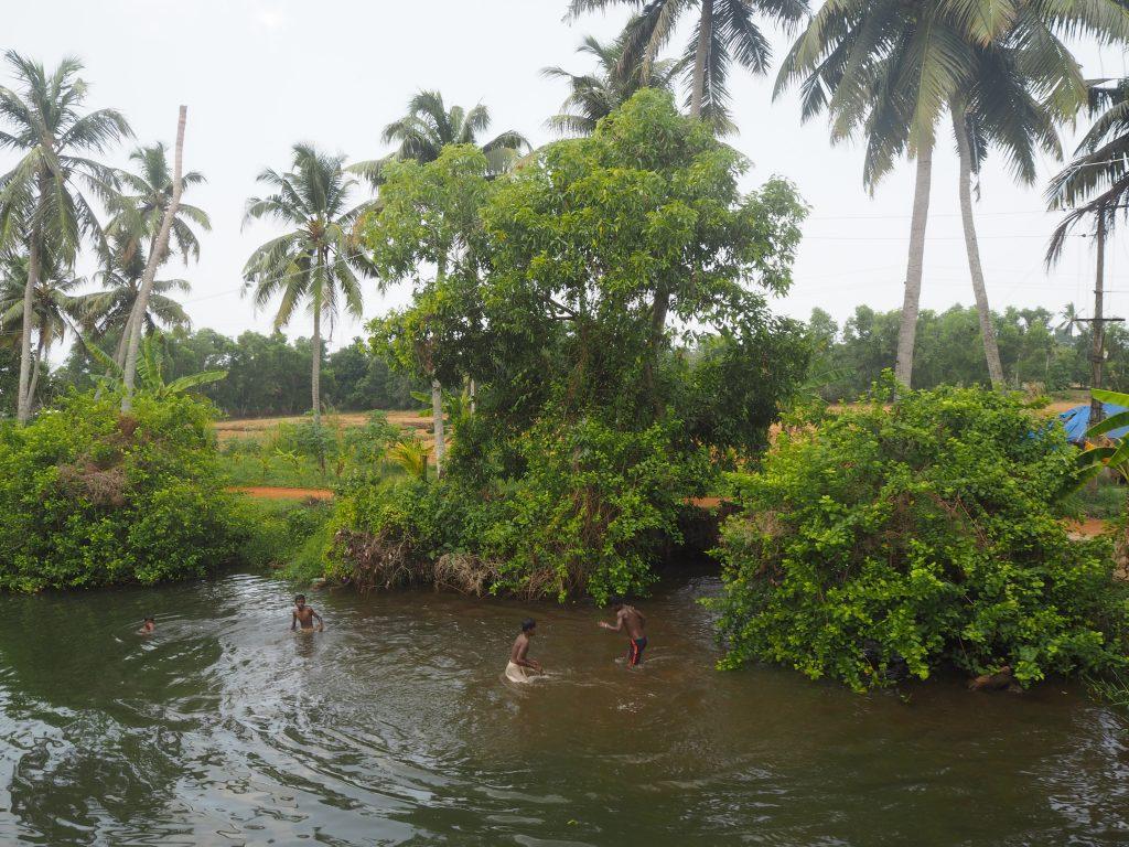川で水遊びをする子供たち。ボートに向かって手を振ってくれる