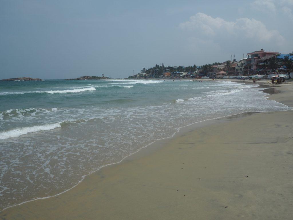 弓形のビーチに淡い青色の海が美しい