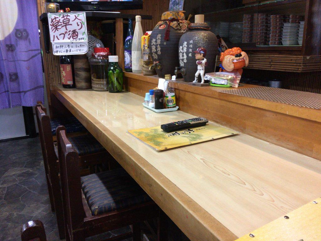 「松乃屋」のカウンター席。ハブ酒があります