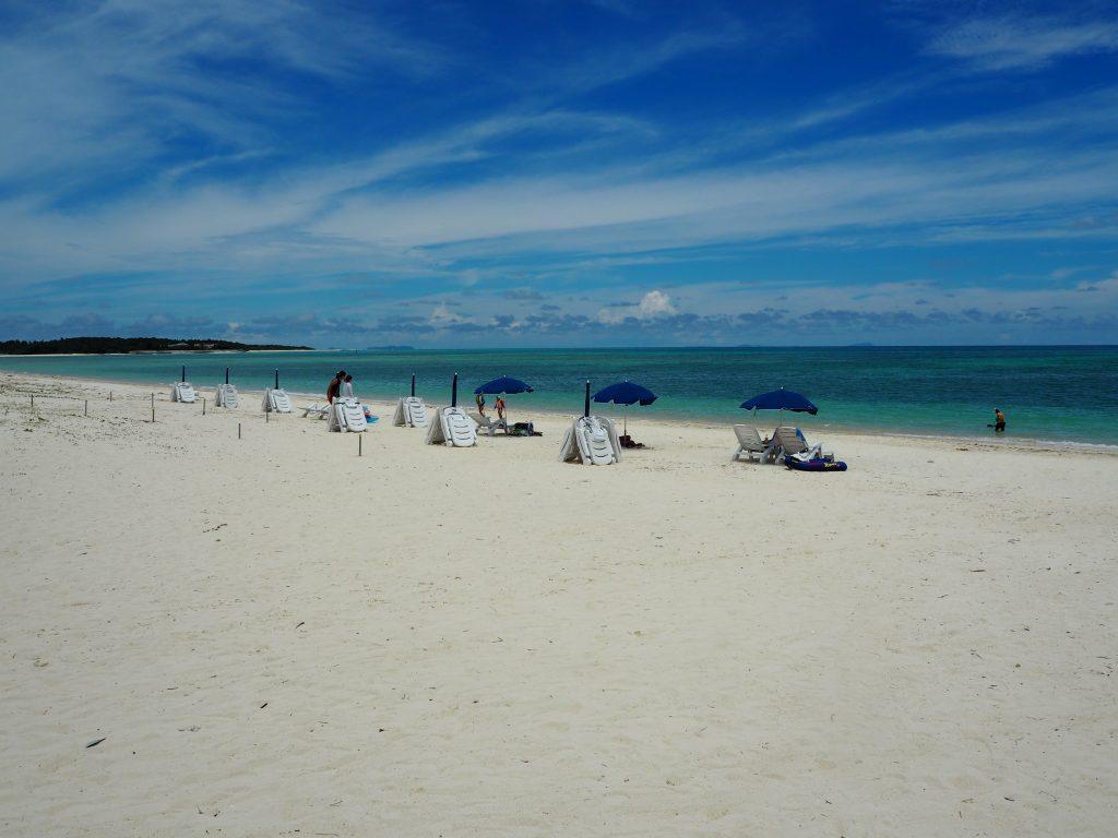 パラソルとビーチチェアーが立ち並ぶ。奥に見えるのは奥武島