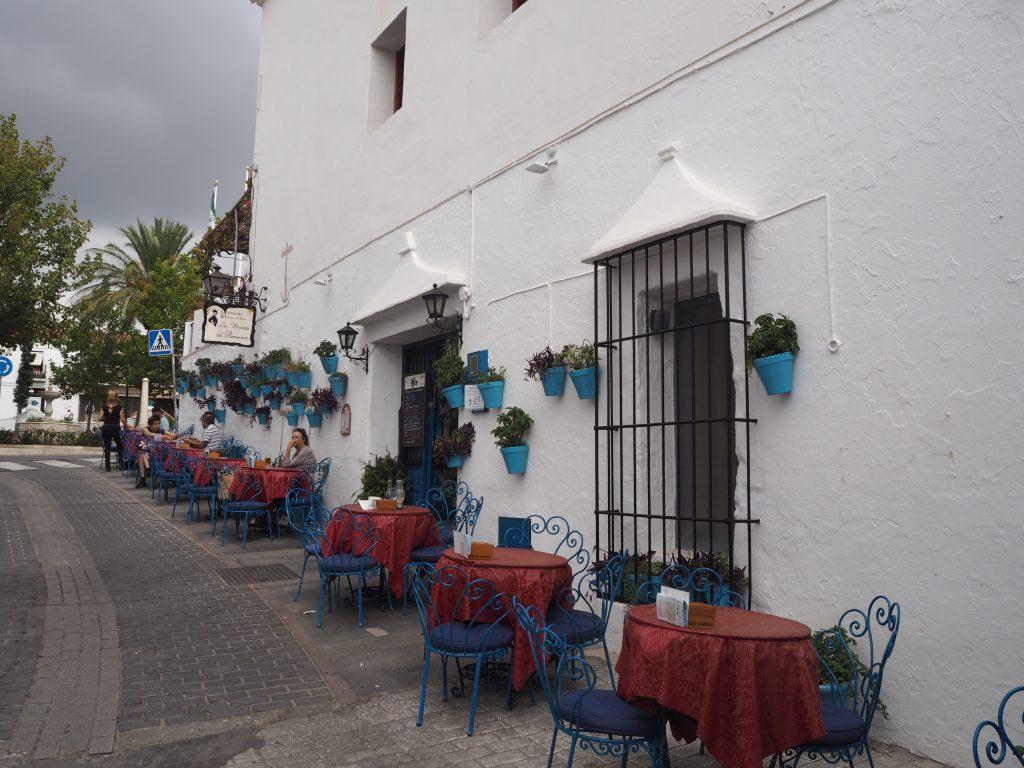 白い壁に青い植木鉢が印象的なおしゃれカフェ