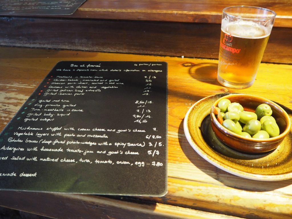 生ビール(1.4ユーロ)とオリーブの実。メニューは英語もある
