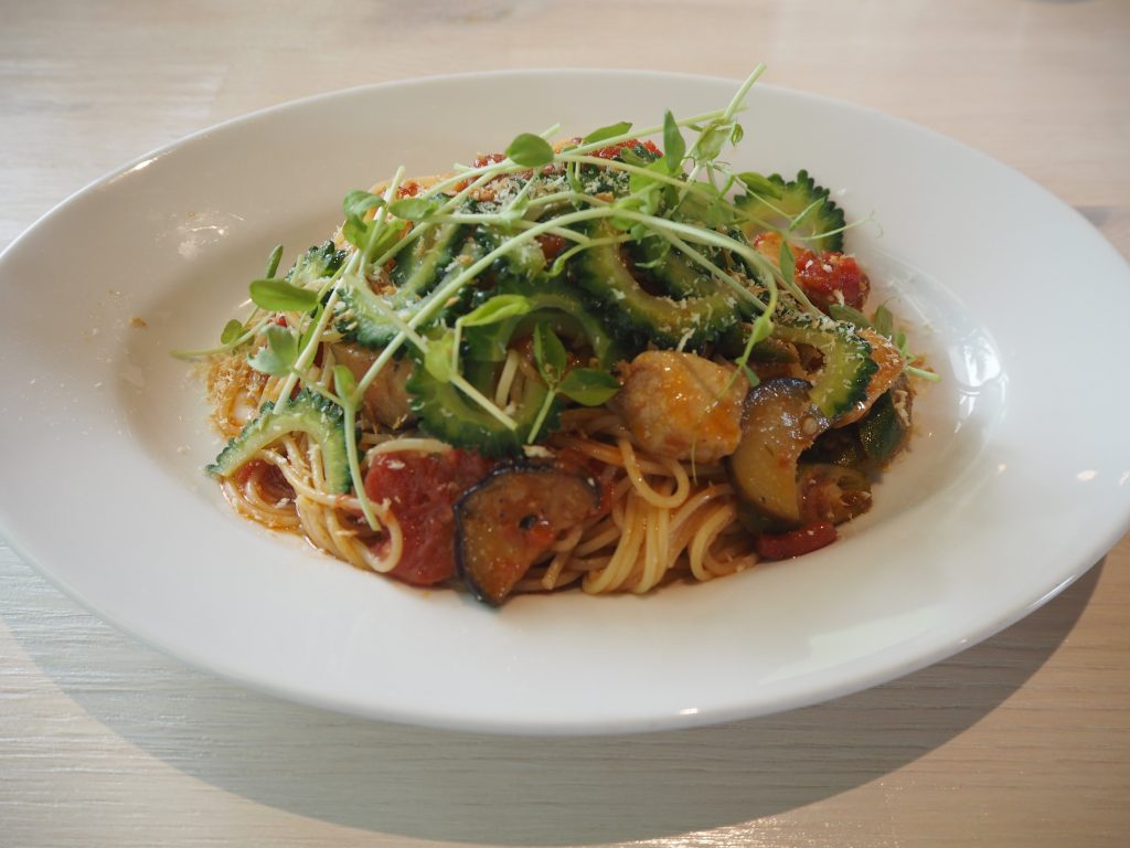 野菜がたっぷり入ったトマトソースパスタ。ゴーヤの苦みが効いている